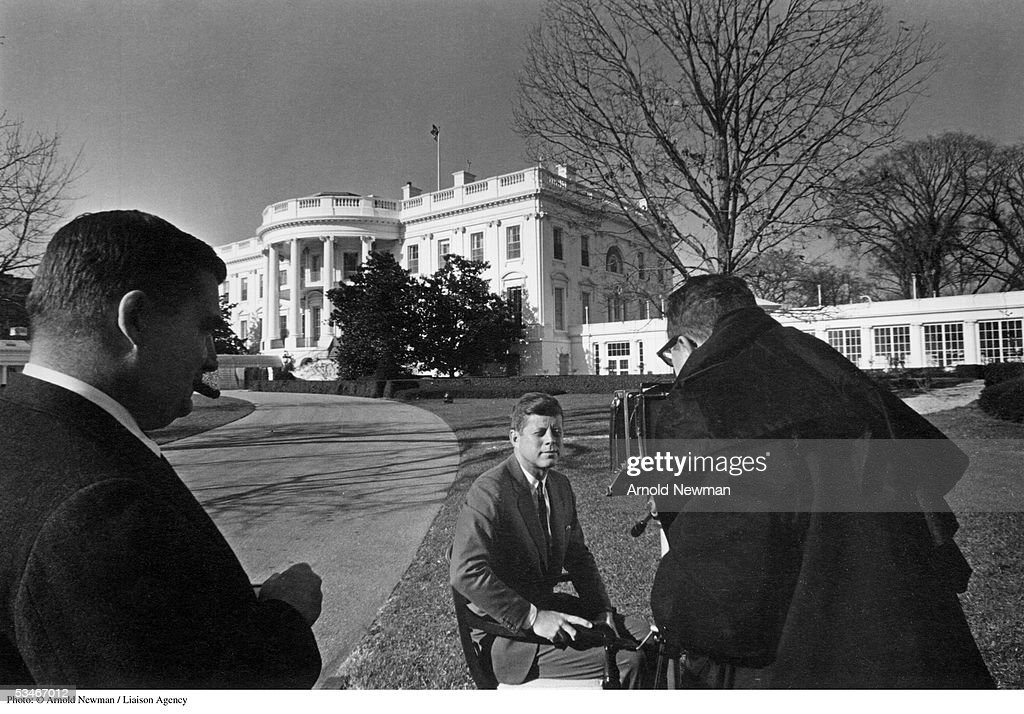 Photographer Arnold Newman photographs President John F. Kennedy in front of the White House, as Press Secretary Pierre Salinger looks on, December 12, 1961 in Washington, DC.