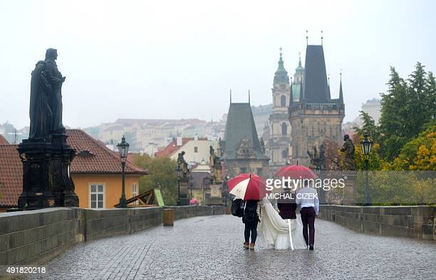A photographer assistant helps a South Korean woman dressed as bride as she walks with her husband across the Charles Bridge early morning on October...