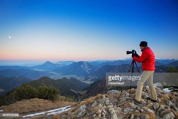 Fotógrafo en la cima de una montaña, en el área de los Alpes