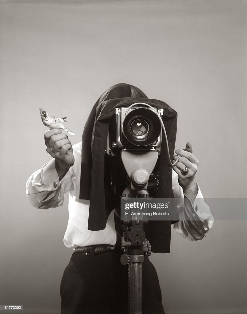 Photographer Behind View Camera Holding A Birdy. : Stock Photo