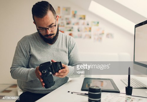 Photographer Changing Lens On His Digital Camera.