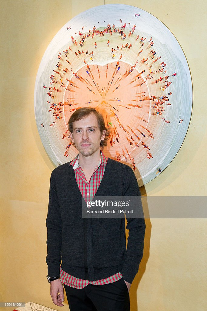Photographer Charles Maze poses by one of his photographs during the 'Sorcieres' (Witches) exhibition preview at Galerie Pierre Passebon on January 8, 2013 in Paris, France.