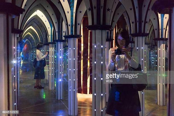 Photographer Cheng Xiaoxian takes photos in a polygonal mirror house as part of the Trick Eye Museum on September 8 2016 in Seoul South Korea The...