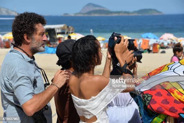 AFP photographer Christophe Simon instructs students from the photography school 'Casa geracao Cidade de deus' in Ipanema Beach in Rio de Janeiro...