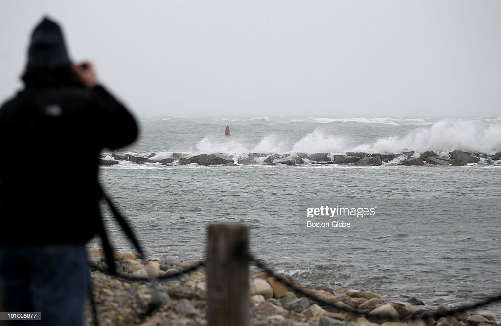 Photographer David J. Kenny gets a few shots of waves breaking over a jetty in Scituate. New England is expecting a Blizzard to bring several feet of snow and high winds.