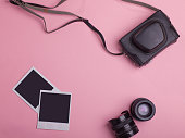 blank photo frames, vintage photo camera bag, lenses around blank copy space isolated on pink background, flat lay