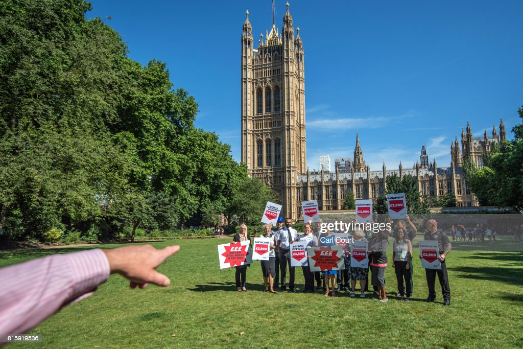 A photographer gestures as Frances O'Grady (blue dress), the General Secretary of the Trades Union Congress (TUC), joins union members at a protest over public sector pay on July 17, 2017 in London, England. The TUC is campaigning for better pay and working conditions for its members.