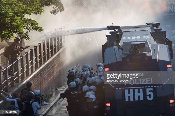 Photographer HansJuergen Burkhard reacts after being sprayed by a water jet of a police water canon a second time while he photographs the 'Welcome...
