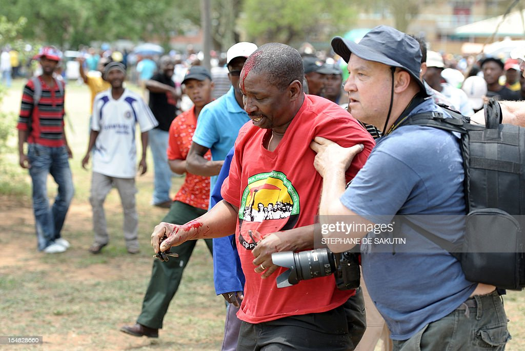A photographer helps an injured man (C) dressed in the red color of the Congress of South African Trade Unions (Cosatu) after he was beaten up by striking miners and as South African police officers fire rubber bullets, stun grenades and tear gas to disperse miners who were trying to prevent a rally organised by the Congress of South African Trade Unions (Cosatu) in Rustenburg, northwest of Johannesburg on October 27, 2012. Bullet casings littered the ground and a helicopter circled above, with police sirens howling, as the protesters were chased into the area surrounding the stadium. The clashes came a day after the National Union of Mineworkers (NUM) announced that it had reached a deal with the world's number one platinum producer Amplats to rehire 12,000 workers who were fired for a wildcat strike. Striking workers are disagree with the deal, which would signal a further winding down of a wave of wildcat strikes that have rocked platinum and gold mines since August. AFP PHOTO / STEPHANE DE SAKUTIN