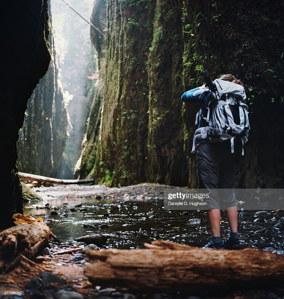 Photographer Hiking in Narrow Gorge