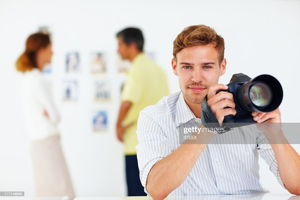 Photographer holding a camera : Stock Photo