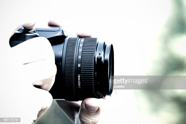 Photographer holding professional camera, high key, copy space
