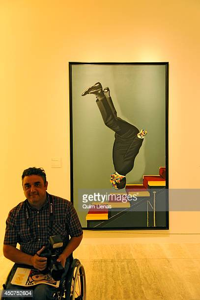 A photographer in a wheelchair passes in front of the painting 'Vestido bajando la escalera' of Eduardo Arroyo during the opening for the press of...