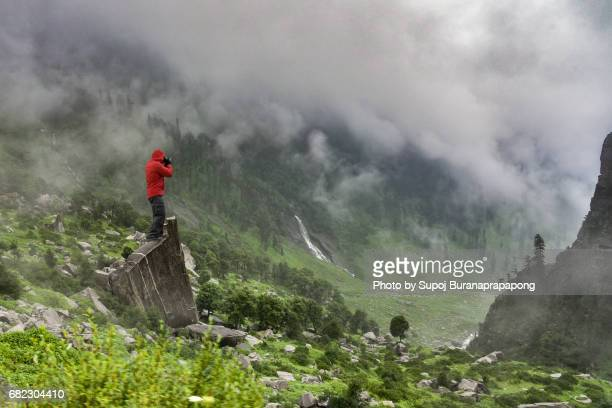 Photographer in red jacket take photo of fog in rainy day on summer at mountain peak of rohtang pass,manali,Himachal Pradesh,India