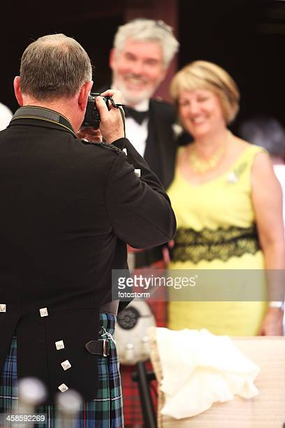 Photographer in Scottish kilt taking a picture of senior couple