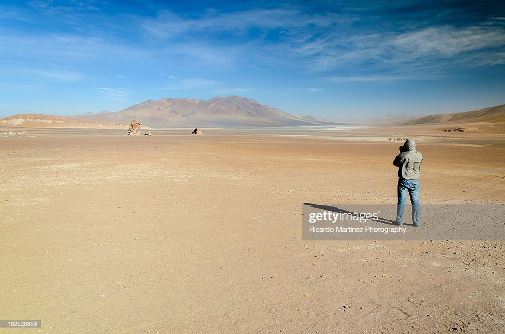 A photographer in the desert : Stock Photo