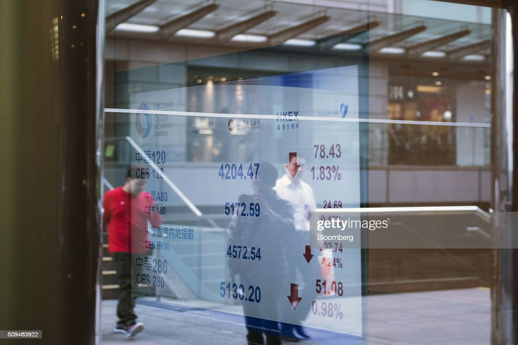A photographer is reflected in a window as a screen displays stock prices at the Hong Kong Exchanges and Clearing Ltd. (HKEx) building in Hong Kong, China, on Thursday, Feb. 11, 2016. Hong Kong stocks headed for their worst start to a lunar new year since 1994 as a global equity rout deepened amid concern over the strength of the world economy. Photographer: Xaume Olleros/Bloomberg via Getty Images