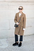 Photographer Jess Bush wears an Yves Saint Laurent bag Dagma coat and top MSGM trousers Stella McCartney shoes and Celine sunglasses on day 3 during...