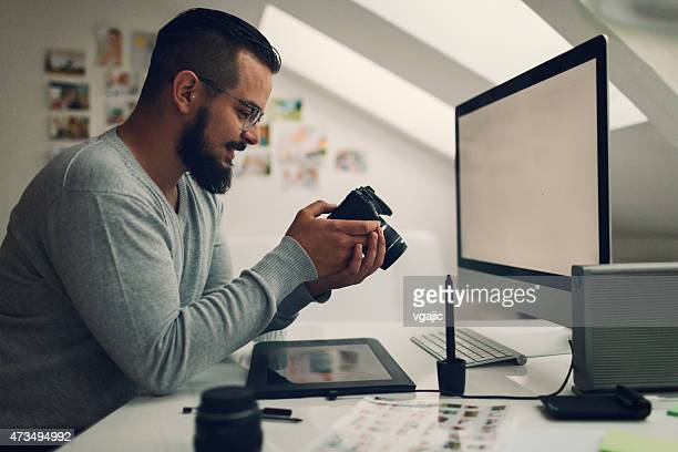 Photographer Looking Images on his Digital Camera in office.