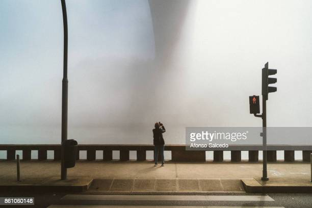 Photographer looking up photographing a foggy bridge in front of her
