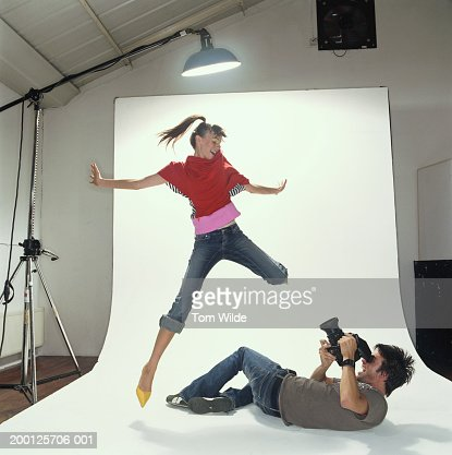 Photographer lying on studio floor taking picture of model jumping : Stock Photo