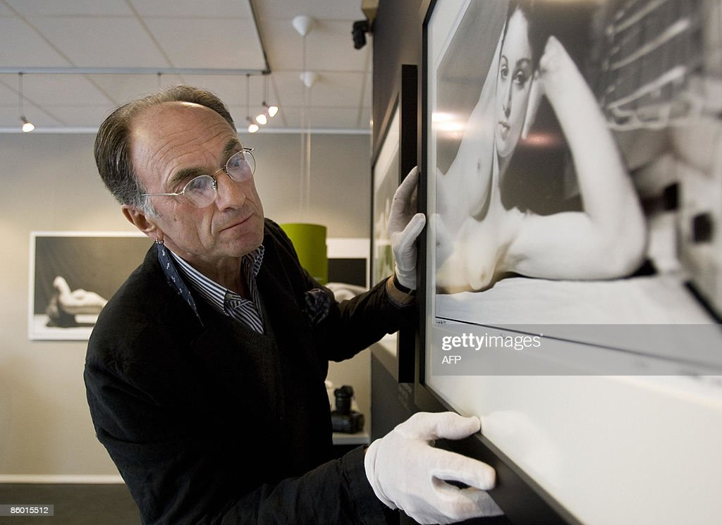 Photographer Martin Schreiber looks at one of his seven nude pictures of Madonna at Galery Art District in Amsterdam, on April 17, 2009. Schreiber took pictures of the famous popstar in 1979 which are exhibited in the Dutch capital until May 22. AFP PHOTO/ANP/ ADE JOHNSON netherlands out - belgium out
