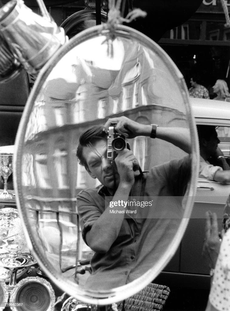 Photographer Michael Ward using a Leica M3 camera to take a self portrait reflected in a silver tray, Portobello Road Market, 1959.