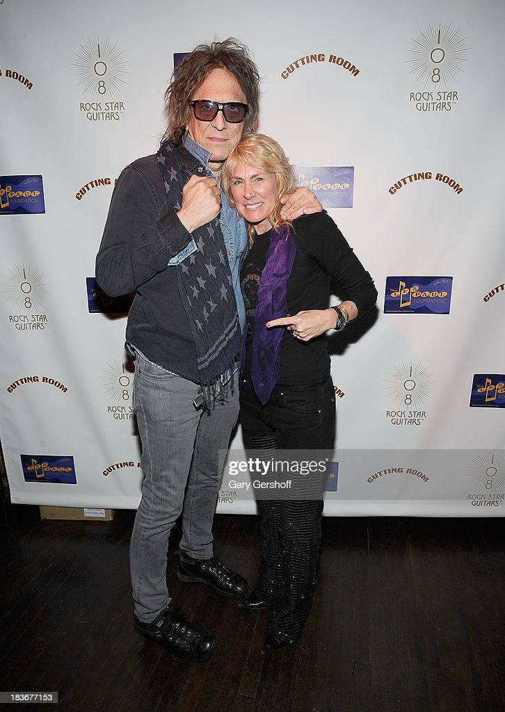 Photographer Mick Rock (L) and author and photographer Lisa Johnson attend the book launch and performance for '108 Rock Star Guitars' benefitting The Les Paul Foundation at The Cutting Room on October 8, 2013 in New York City.