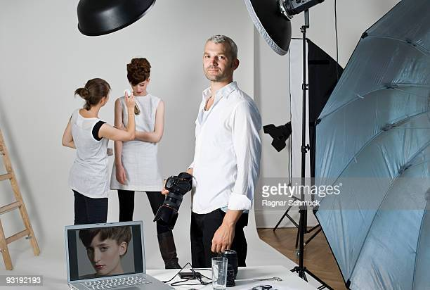A photographer, model and make-up artist on set of a fashion shoot