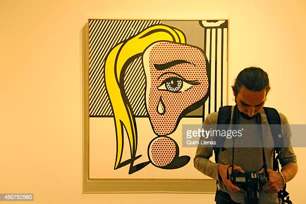 A photographer passes in front of the painting Girl with a Tear III of Roy Lichtenstein during the opening for the press of Pop Art Myths exhibition...