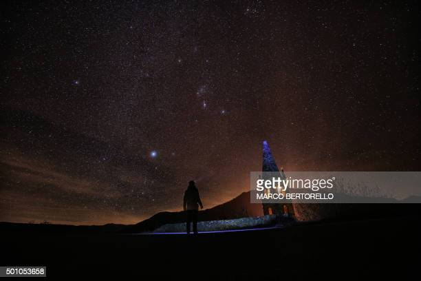 TOPSHOT A photographer prepares to take pictures of the annual Geminid meteor shower on the Elva Hill in Maira Valley near Cuneo northern Italy on...