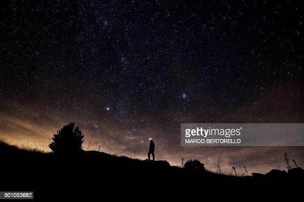 A photographer prepares to take pictures of the annual Geminid meteor shower on the Elva Hill in Maira Valley near Cuneo northern Italy on December...