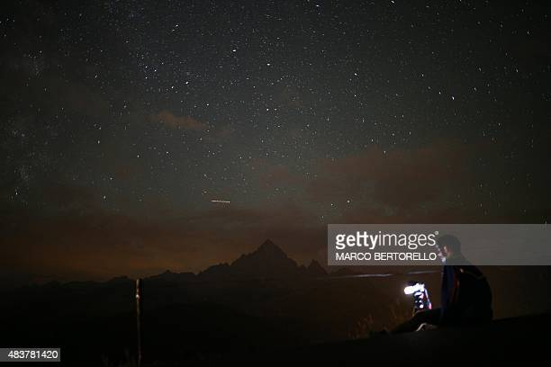 A photographer prepares to take pictures of the annual Perseid meteor shower in the village of Crissolo near Cuneo in the Monviso Alps region of...