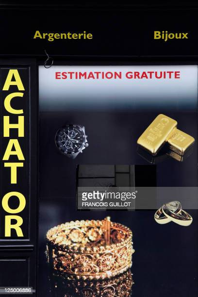 A photographer reflects himself in the window of a shop that buys sales and estimates gold and jewllery on September 8 2011 in Paris AFP PHOTO...