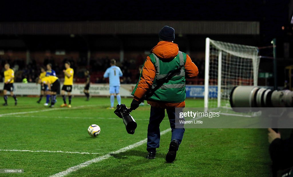 A photographer returns the ball as no ball boy at hand during the npower League Two match between AFC Wimbledon and Port Vale at The Cherry Red Records Stadium on January 24, 2013 in Kingston upon Thames, England.