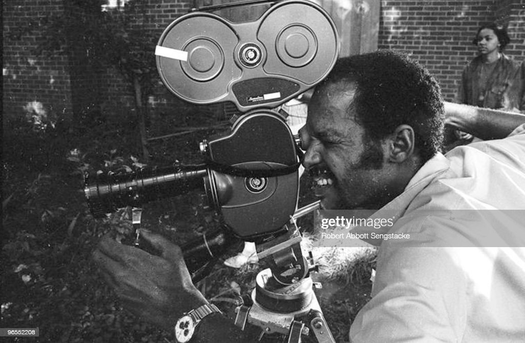 Photographer Robert Abbott Sengstacke looks through the film camera while assisting on the set of one of Carlton Moss' films, Nashville, 1972. Student Gloria Brown from Fisk University's Film Program is visible in the background.