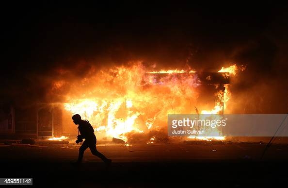 A photographer runs by a burning building during a demonstration on November 25 2014 in Ferguson Missouri Ferguson has been struggling to return to...