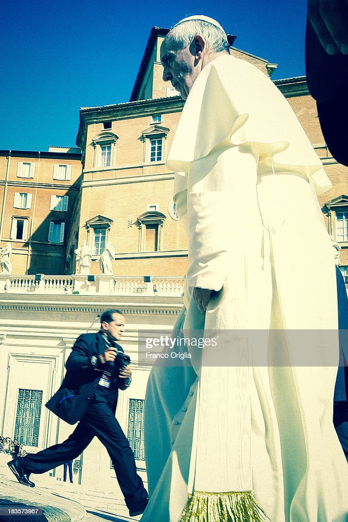 A photographer runs in front of <a gi-track='captionPersonalityLinkClicked' href=/galleries/search?phrase=Pope+Francis&family=editorial&specificpeople=2499404 ng-click='$event.stopPropagation()'>Pope Francis</a> as he attends his weekly General Audience in St. Peter's Square on September 18, 2013 in Vatican City, Vatican. After the success of his Social networking accounts of Twitter and Facebook, <a gi-track='captionPersonalityLinkClicked' href=/galleries/search?phrase=Pope+Francis&family=editorial&specificpeople=2499404 ng-click='$event.stopPropagation()'>Pope Francis</a> joined Instagram, reporting today more than 8000 followers.