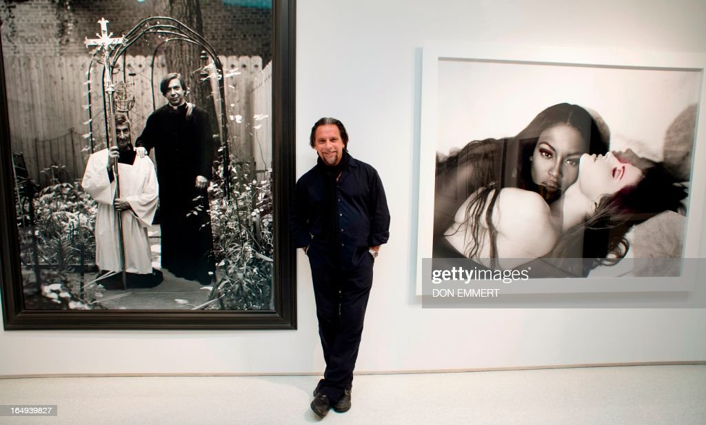 Photographer Sante D'Orazio poses between two of his photographs on March 29, 2013 at Christie's in New York. D'Orazio's photos are part of 'Photographs Week at Christie's.' ++RESTRICTED TO EDITORIAL USE, MANDATORY MENTION OF THE ARTIST UPON PUBLICATION, TO ILLUSTRATE THE EVENT AS SPECIFIED IN THE CAPTION++ AFP PHOTO/Don Emmert