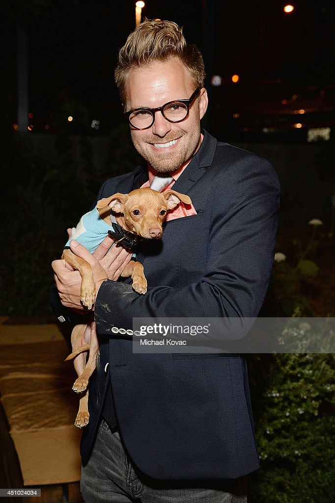 Photographer Seth Casteel with dog Tuna (aka TunaMeltsMyHeart) enjoys the 'More Than a Cone' art auction and campaign launch benefiting Best Friends Animal Society in Los Angeles where renowned artists re-imagined the 'cone of shame' to raise awareness for animals in need at LA Plaza de Cultura y Artes on June 21, 2014 in Los Angeles, California.