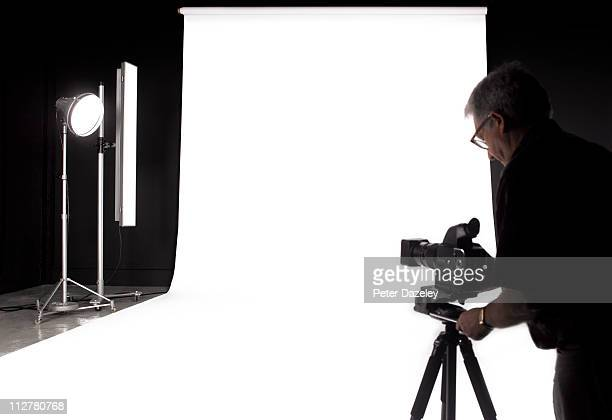 Photographer setting up digital camera in studio