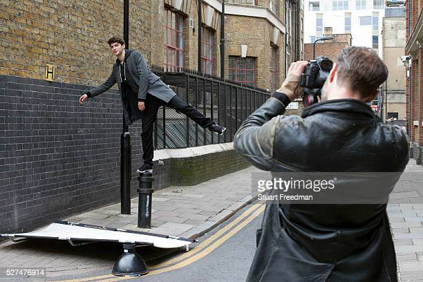 A photographer shoots a model as he balances on a bollard during a fashion shoot in the streets of Shoreditch London UK Shoreditch an area that was...