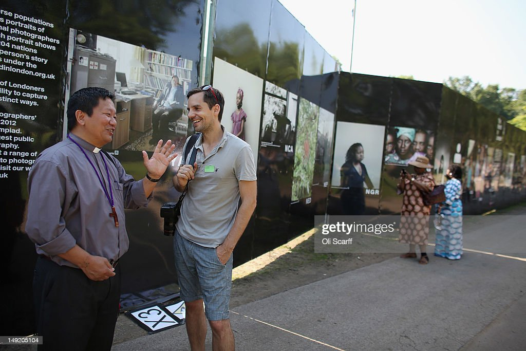 Photographer Simon Roberts (2nd L) chats to Reverend David Haokip, from Myanmar, in front of Mr Roberts' portrait of Mr Haokip in the photography exhibition 'The World in London' in Victoria Park on July 25, 2012 in London, England. The project, initiated by The Photographers' Gallery, aimed to commission portraits of 204 Londoners, each originating from one of the nations competing in the London 2012 Olympic Games. The project has taken three years to come to fruition and the Photographers' Gallery is still seeking to find sitters from six nations to complete the full set, namely: American Samoa, FS Micronesia, Guam, Marshall Islands, Nauru and Palau.