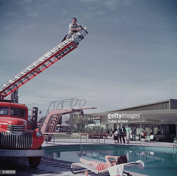 Photographer Slim Aarons photographing film starlet Mara Lane from the top of an extending ladder by the swimming pool at Sands Hotel Las Vegas
