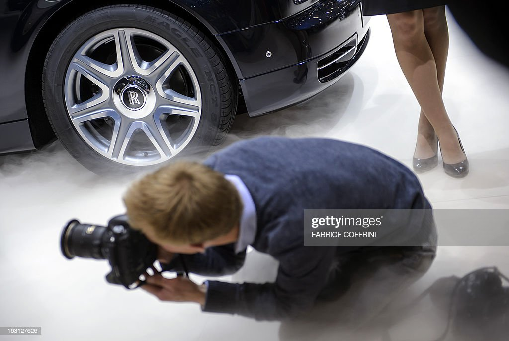 A photographer snaps pictures at the Rolls Royce car maker's booth on March 5, 2013 on the press day of the Geneva car Show in Geneva. The Geneva International Motor Show opened its doors to the press under a dark cloud, with no sign of a speedy rebound in sight for the troubled European market. The event, which is considered one of the most important car shows of the year, will again be heavily marked by the crisis in Europe after an already catastrophic year in 2012.
