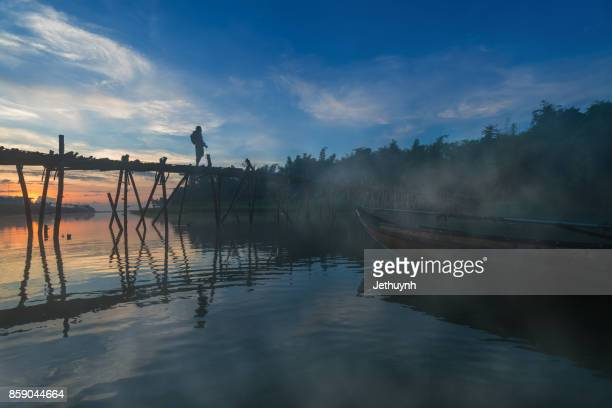 Photographer stand in Bamboo bridge at countryside Quang Ngai Vietnam in the early morning