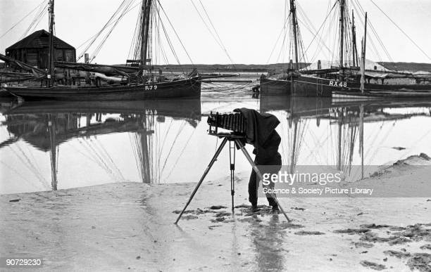 Photographer standing on an estuary mudflat taking a photograph c 1900s