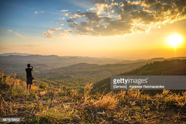 Photographer standing on the hill in the sunset