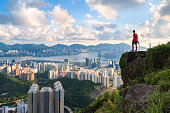 photographer standing on the top of Cliff above Hong kong cityscape