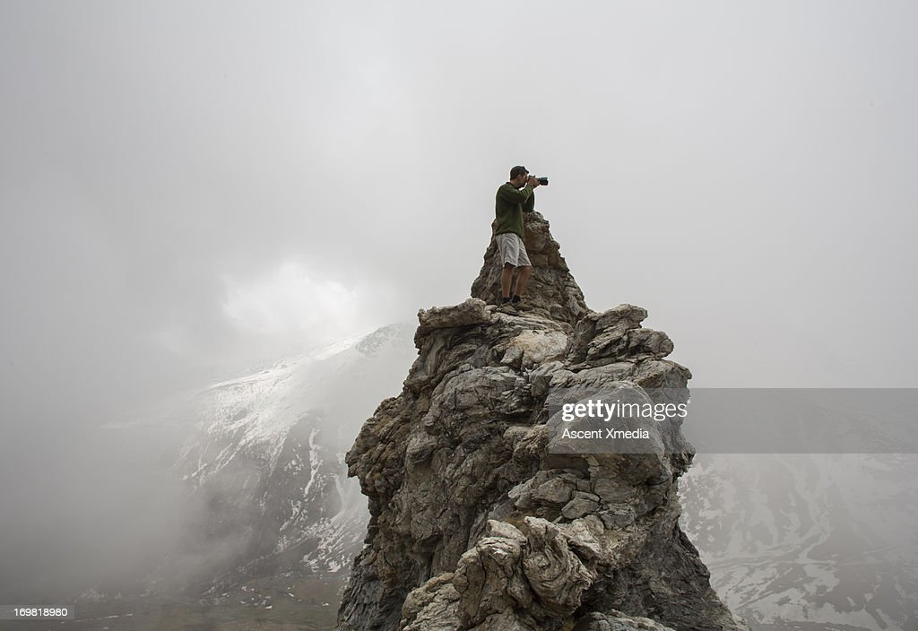 Photographer stands on rock pinnacle, mtns and fog : Stock Photo